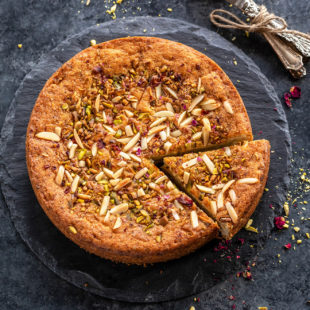 a round eggless mawa cake decorated with nuts and rose petals on top with few spoons placed on the side