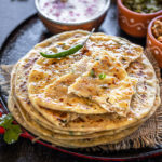 stack of paneer paratha with green chili on the side and bowls of yogurt, pickle in the background