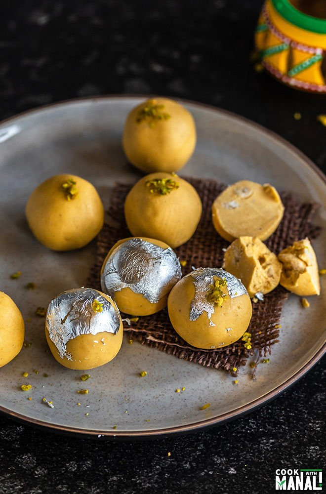 besan ladoo placed in a plate with few them of broken to show the inside