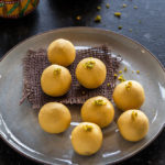8 pieces of besan ladoo arranged in a round plate