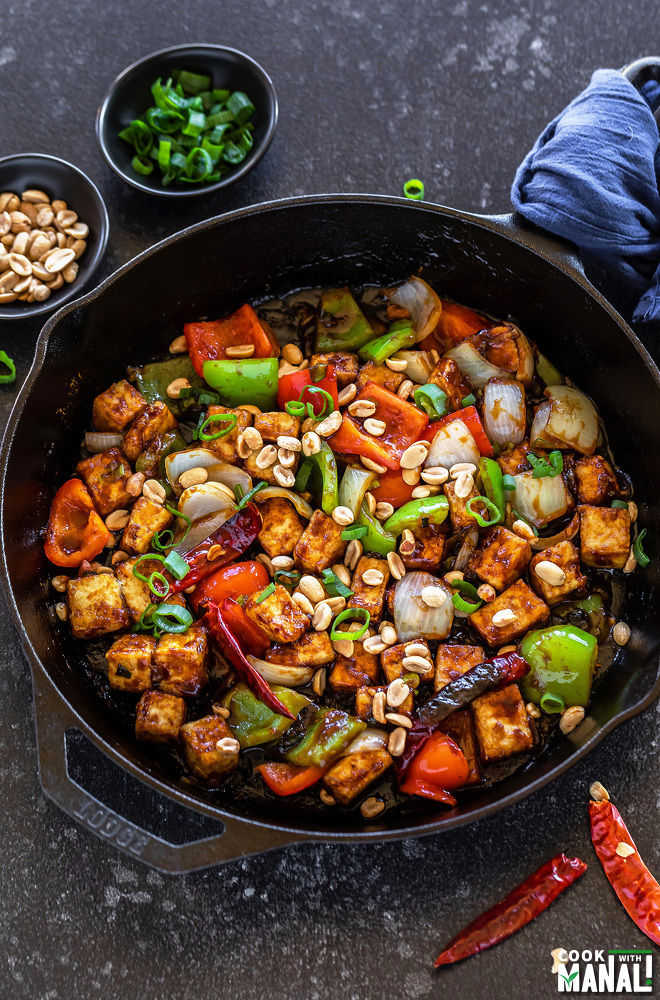 kung pao tofu served in a cast iron skillet with bowls of peanuts and chopped green onions placed in the background