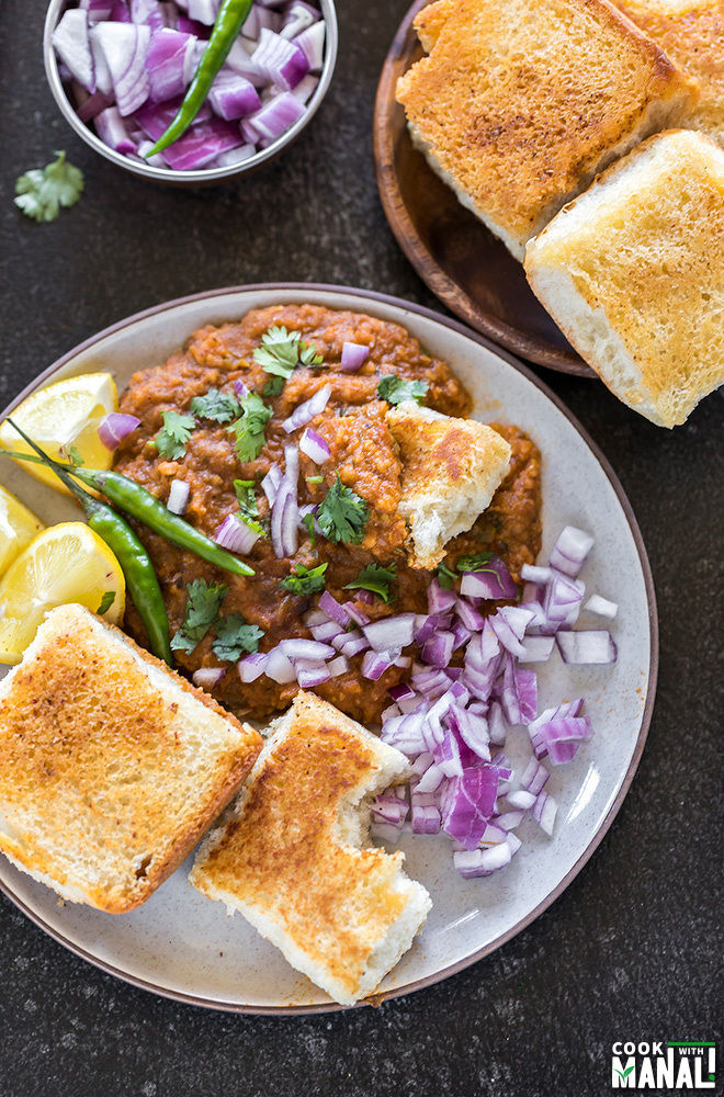 pav bhaji in a round plate served with a side of green chili, lemon slices and chopped onions
