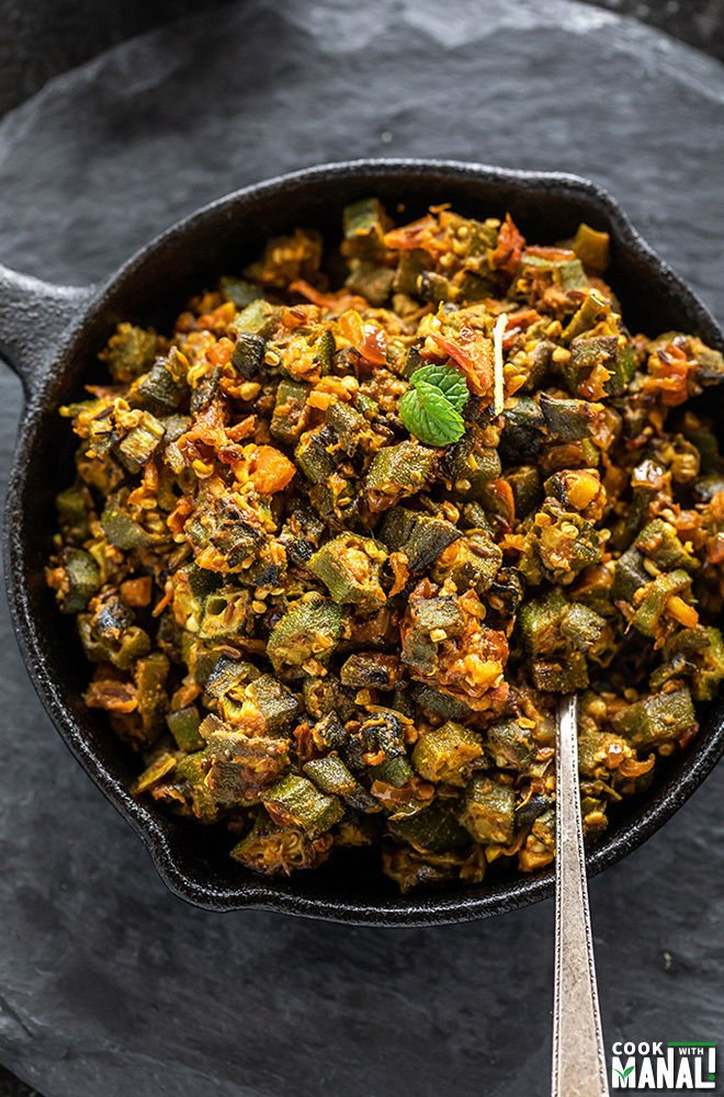 Bhindi Masala in a small iron skillet with a spoon