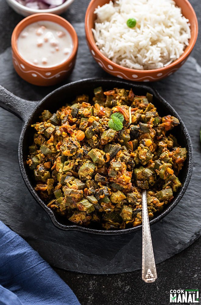 Bhindi Masala in a small iron skillet with a spoon with bowl of rice in the background