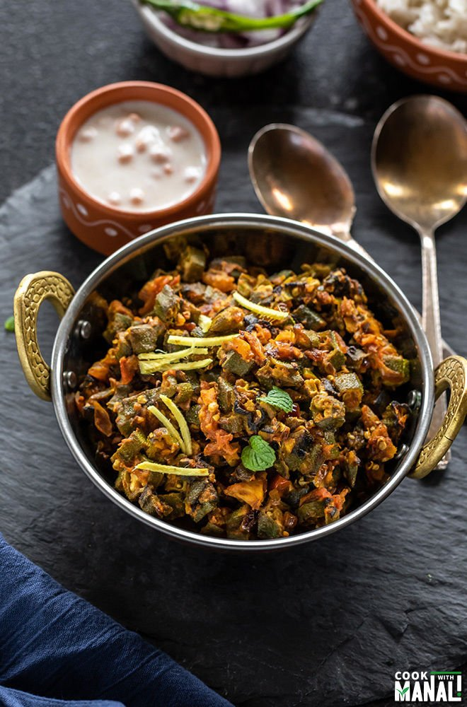 bhindi masala in a small copper kadai with 2 spoon on the side and bowl of yogurt in the background