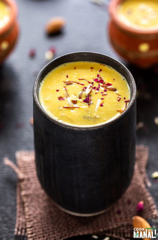 badam milk served in a black glass and garnished with saffron