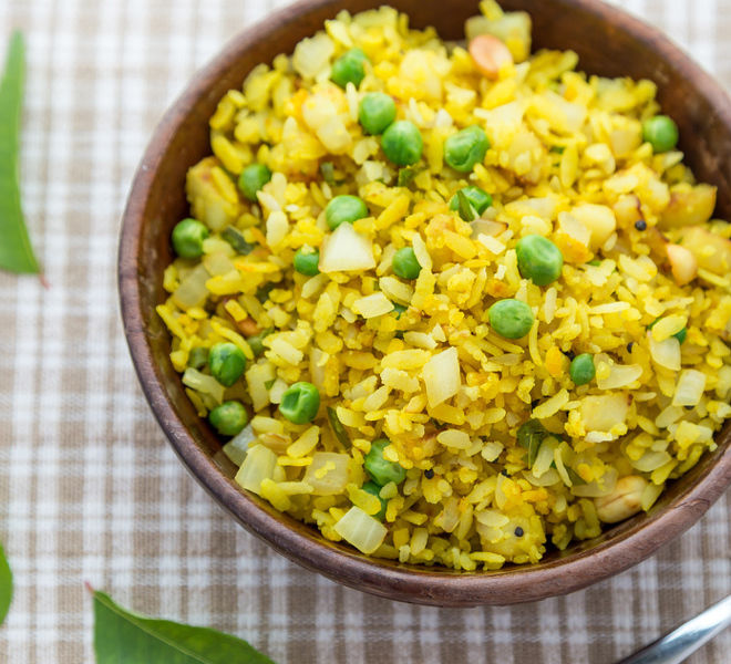 poha in a wooden bowl with curry leaves scattered on the sides