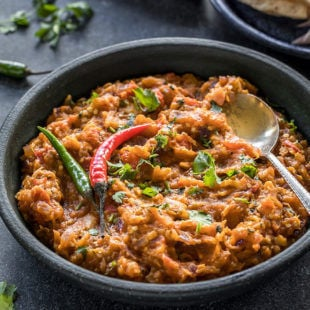 baingan bharta served in a black bowl garnished with green chilies and a spoon on the side