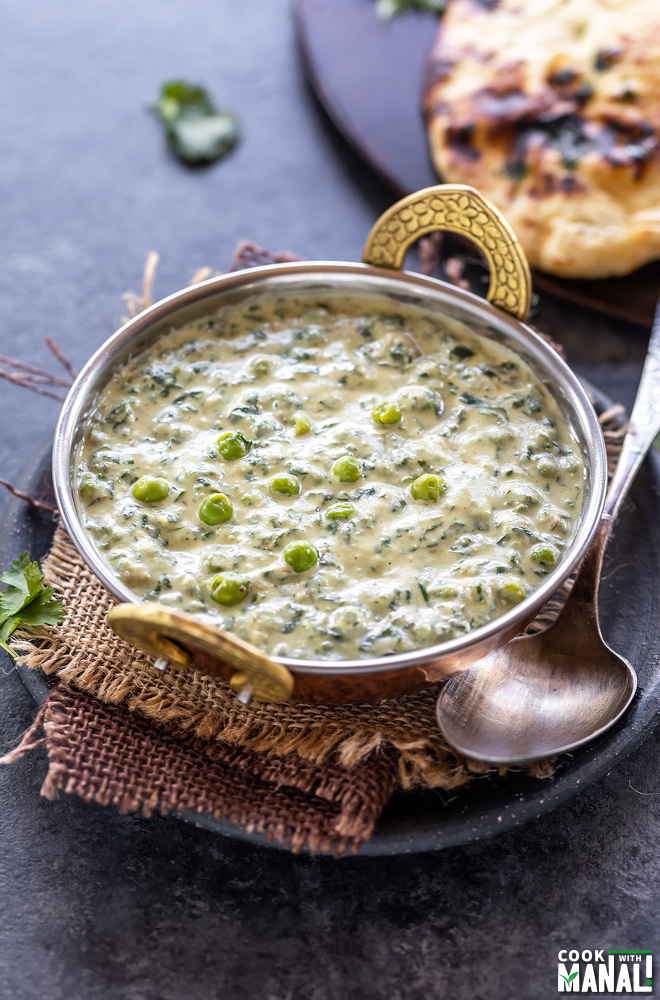 methi matar malai served in a copper kadai with a naan placed in the back