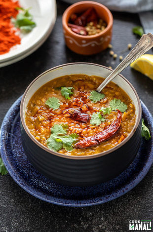 dal tadka in a black bowl garnished with cilantro with a spoon and some spices in the background