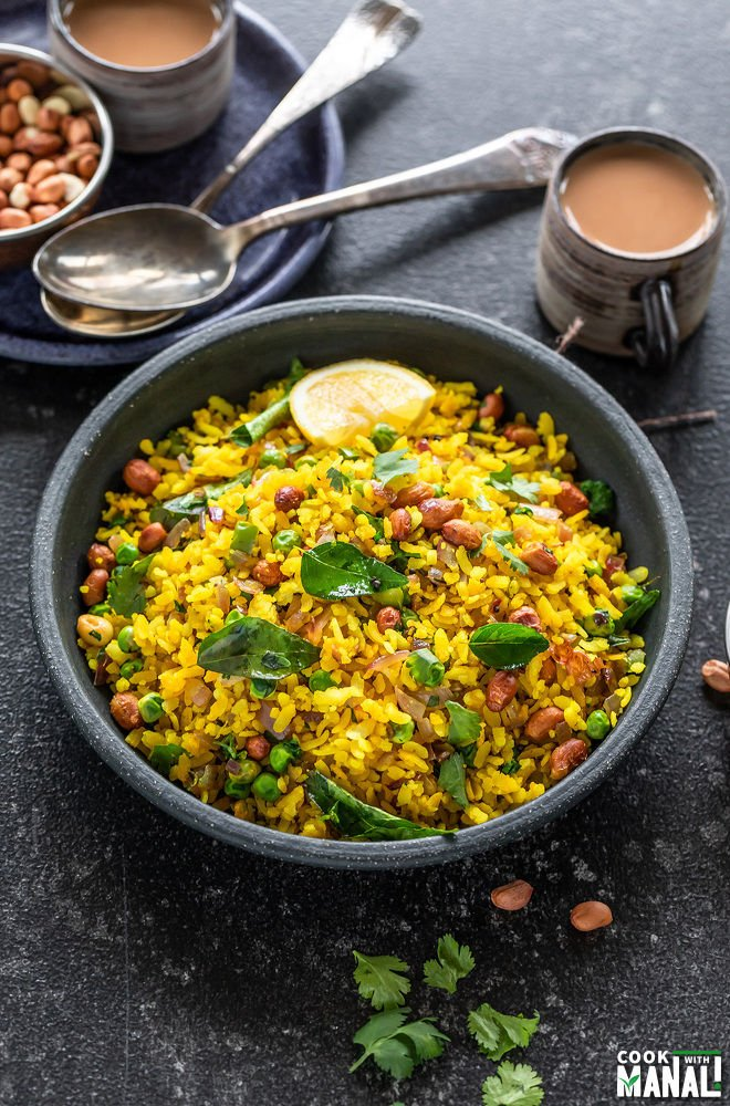 poha served in a black bowl garnished with cilantro and lemon wedges with cups of chai placed in the background
