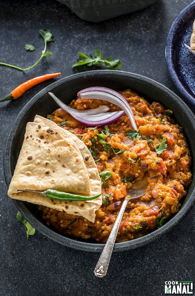 punjabi baingan bharta served in a black bowl with rotis on the side