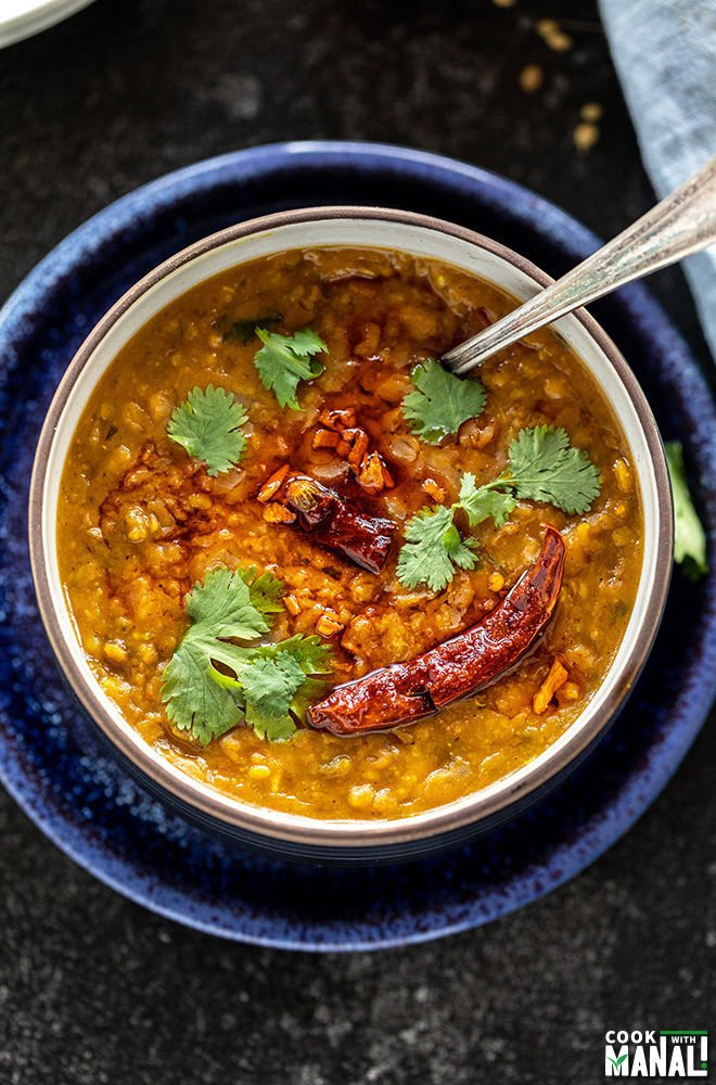 bowl of dal tadka garnished with cilantro with a spoon