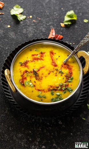 moong dal tadka in a copper kadai with a garnish of cilantro and cumin