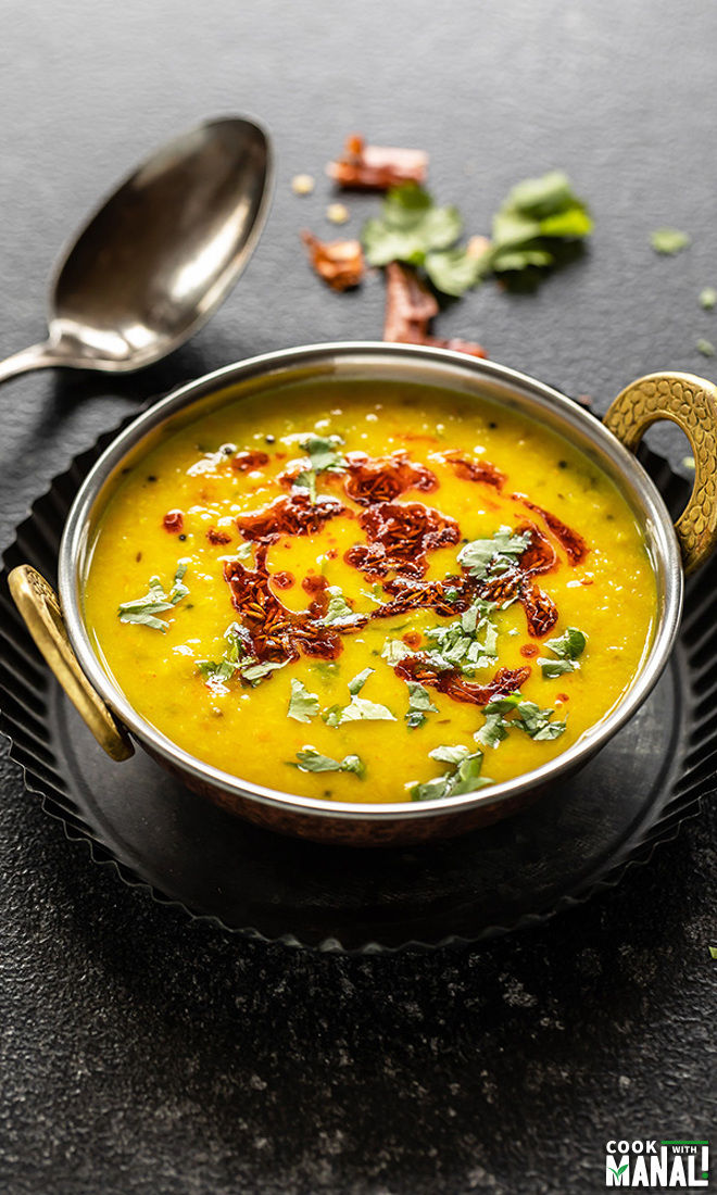 moong dal served in a copper kadai garnished with a tadka of oil and cumin seeds with serving spoon in the background