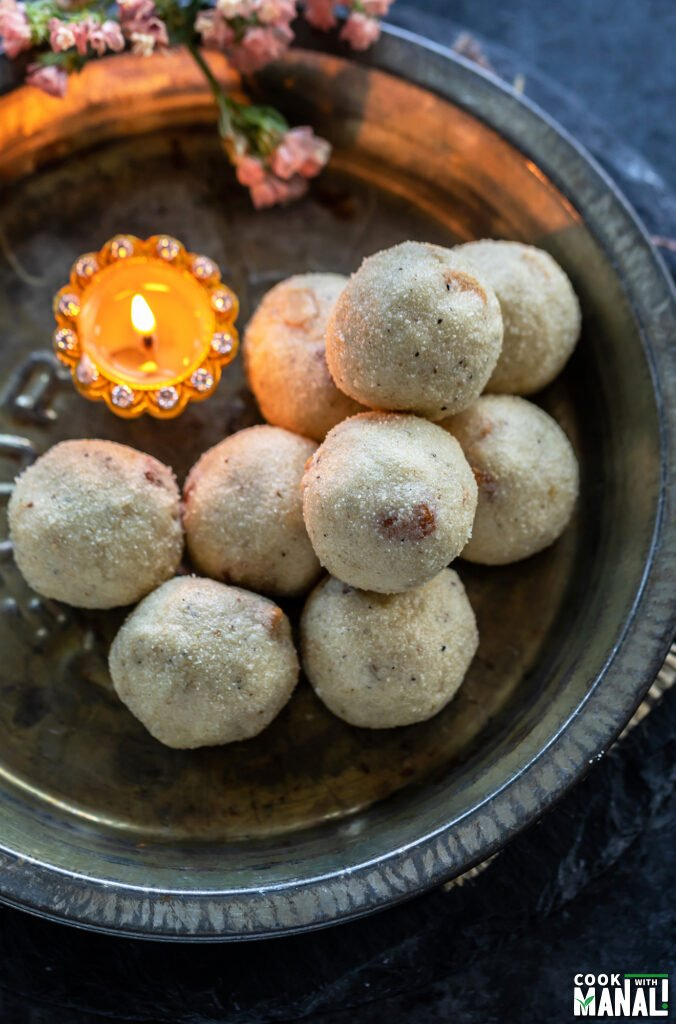 rava ladoos stacked on a plate with a diya placed on the side