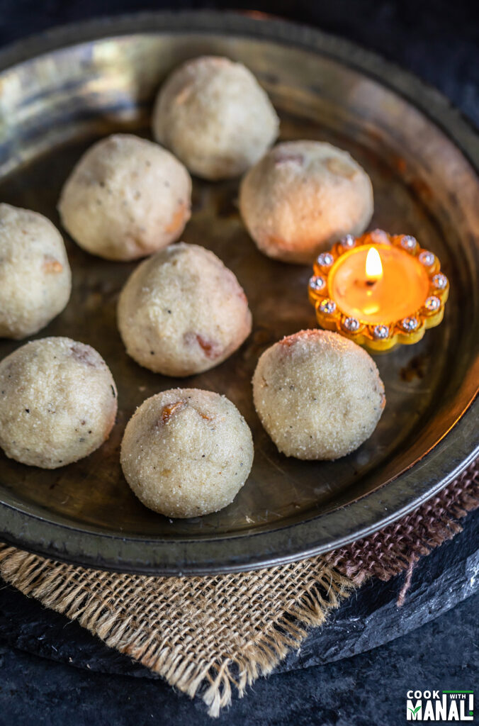 ladoos arranged on a plate with a diya placed on the side