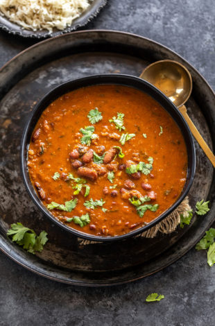 Kidney beans curry served in a black bowl garnished with cilantro with a golden color ladle placed on the side of the bowl
