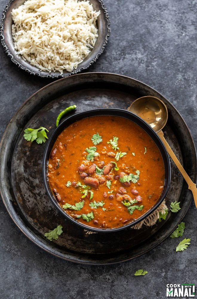 Kidney beans curry served in a black bowl garnished with cilantro with a golden color ladle placed on the side of the bowl and a plate of rice in the background