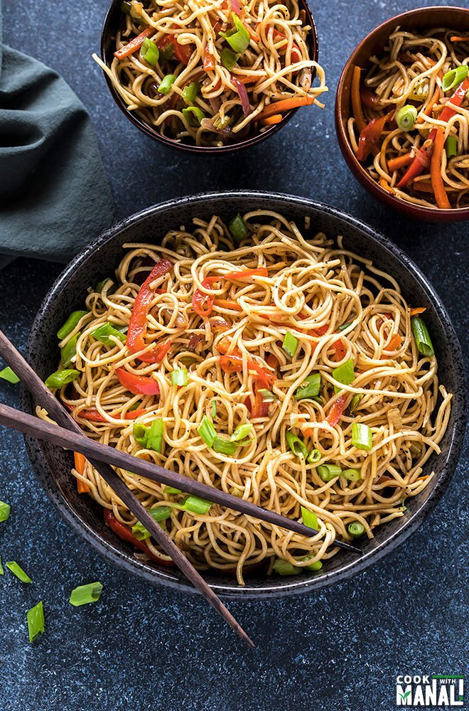 hakka noodles in a black bowl with a pair of chopsticks