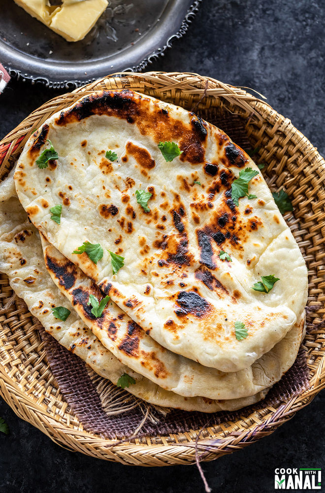 homemade naan stacked and placed on a round bamboo bowl