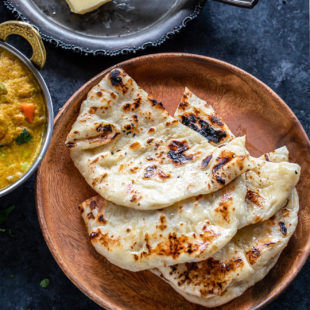 3 pieces of homemade naan placed one over another on a brown plate with a curry placed on the side and a slab of butter in the background