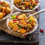 three bowls of sweet potato chaat topped with pomegranate, cilantro and sev