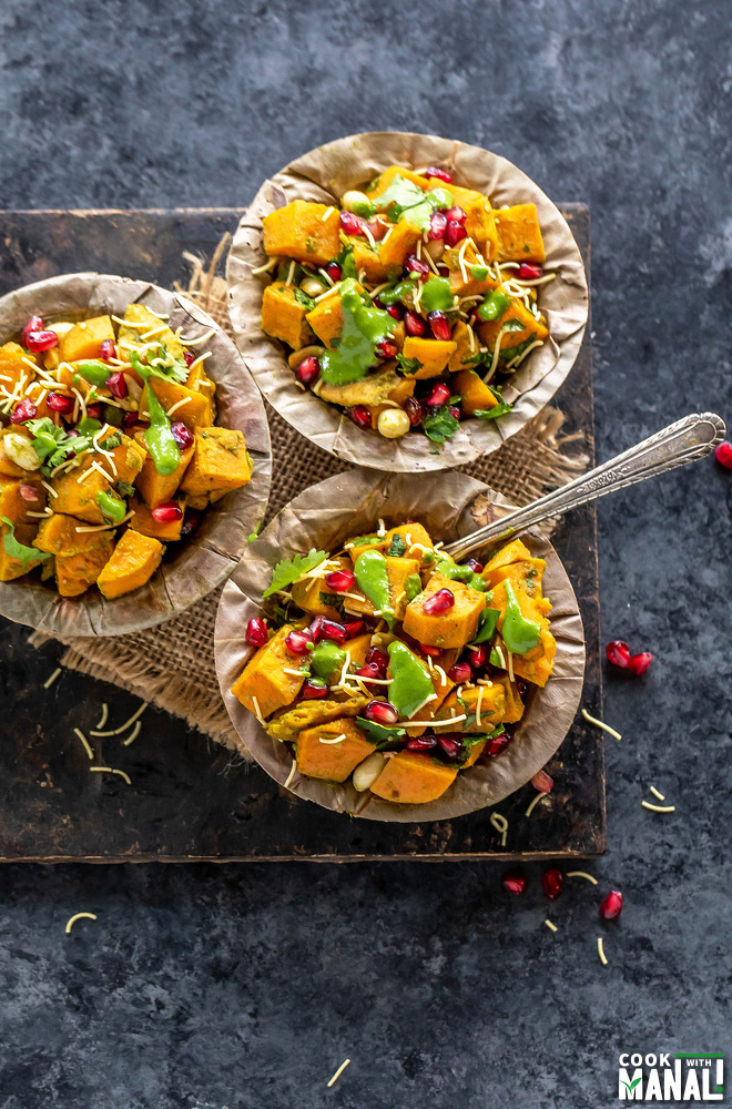 overhead shot of three bowl of sweet potato chaat arranged on a board
