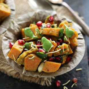 bowl of diced sweet potatoes topped with chutney, pomegranate seeds, cilantro