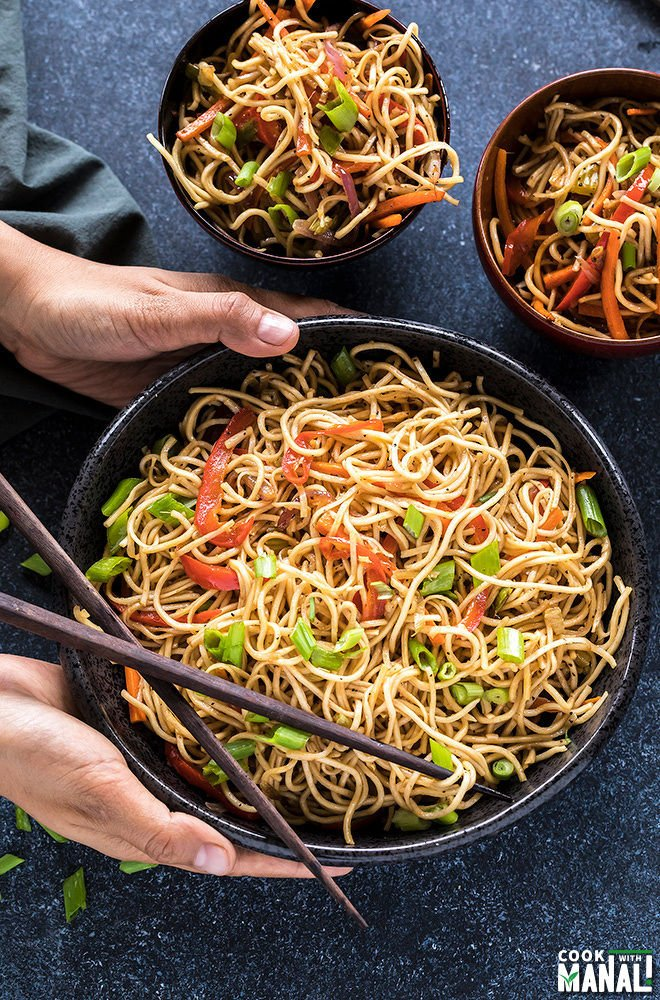 pair of hands holding a bowl of hakka noodles with chopsticks