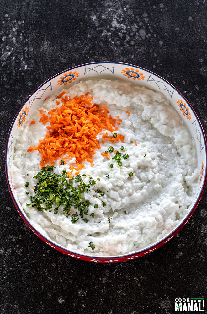 a large bowl with cooked rice mixed with yogurt and grated carrots, cilantro and green chilies