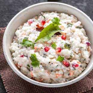 south indian style curd rice in a white bowl garnished with pomegranate arils