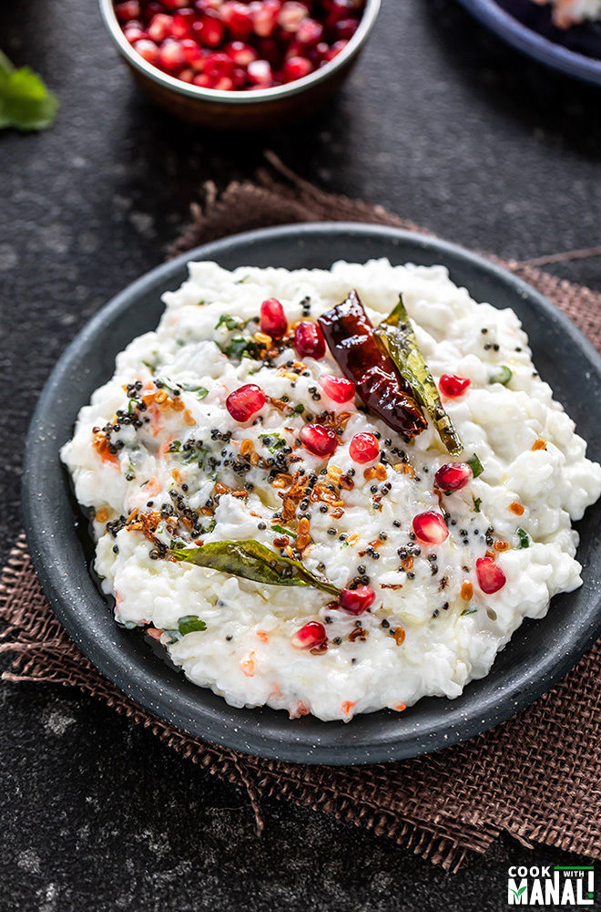curd rice in a black plate garnished with pomegranate and a bowl of pomegranate arils in the background