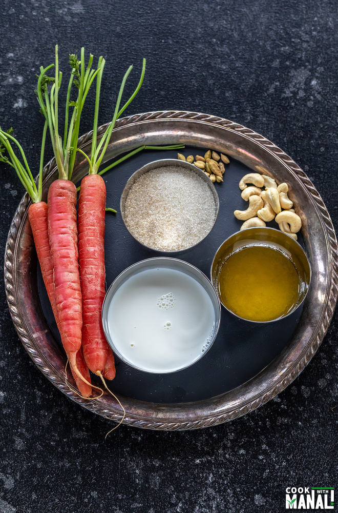 red carrots, sugar, milk, ghee, cashews and cardamom placed on a plate