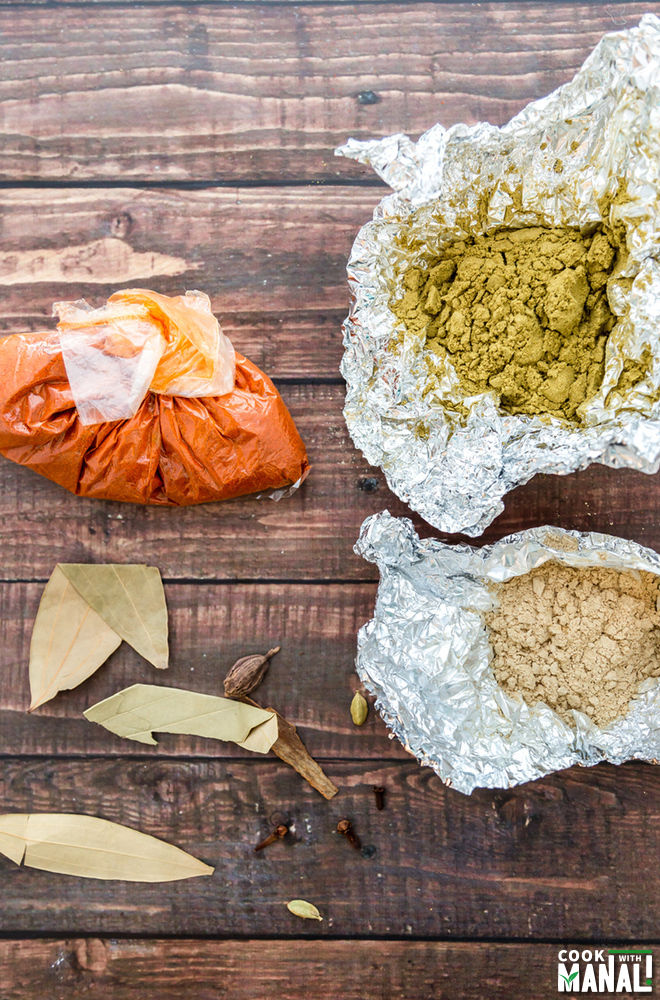 photograph of packets of spices like fennel powder, bay leaf, ginger powder and red chili powder
