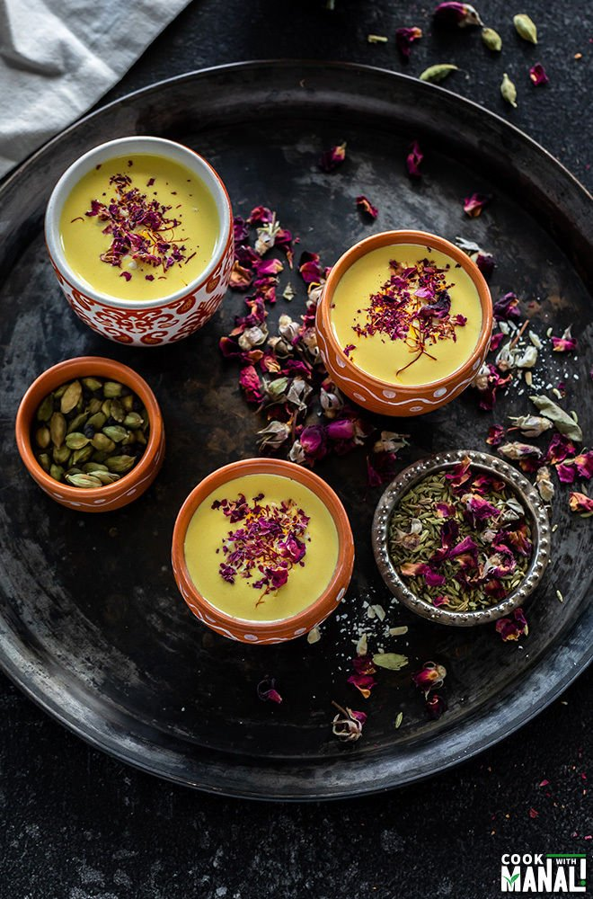 3 small clay pots filled with thandai arranged on a black antique plate with two small bowls filled with rose petals and cardamom on the sides