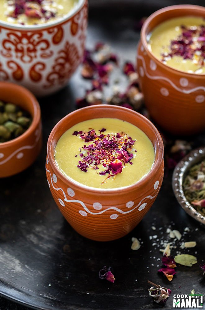 thandai in a small clay pot with small bowls with rose petals, cardamom on the sides and more clay pots of thandai in the backround