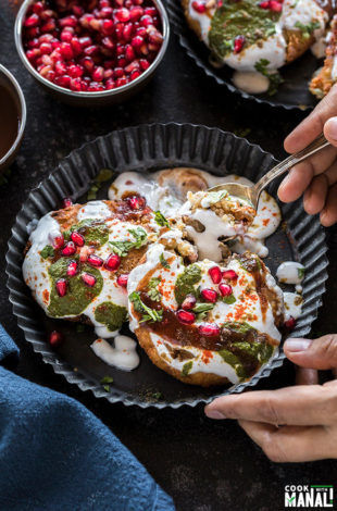 two aloo tikki served in a black rimmed plate and covered with yogurt, chutney and garnished with cilantro and pomegranate seeds