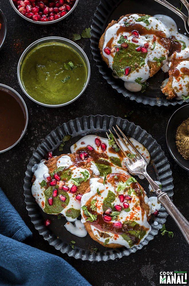 plate of aloo tikki with smalls bowls of chutney, spices all around