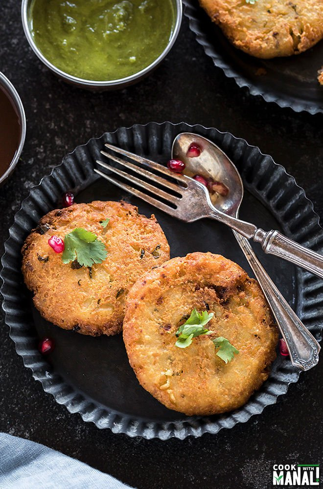 two pieces of aloo tikki in a rimmed plate along with a spoon and fork