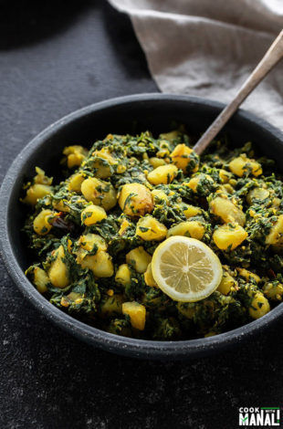 aloo palak in a black bowl with a spoon and served with a lemon wedge