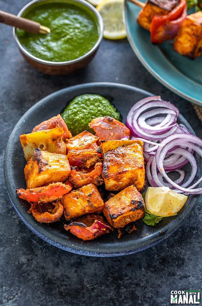 paneer tikka served with onion slices, cilantro chutney and slice of lemon in a black round plate