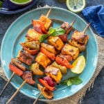 paneer tikka skewers arranged on a blue plate with lemon wedge on the side and bowl of cilantro chutney in the background