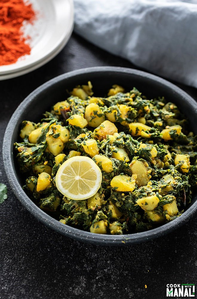 aloo palak in a black bowl with a slice of lemon and spices in the background