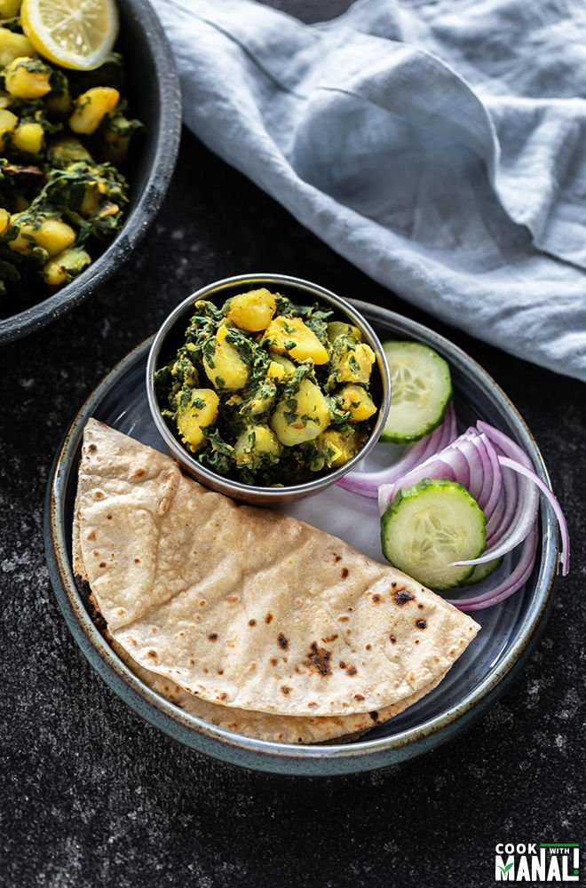 a small blue plate with a bowl of aloo palak, roti, sliced onions and cucumber