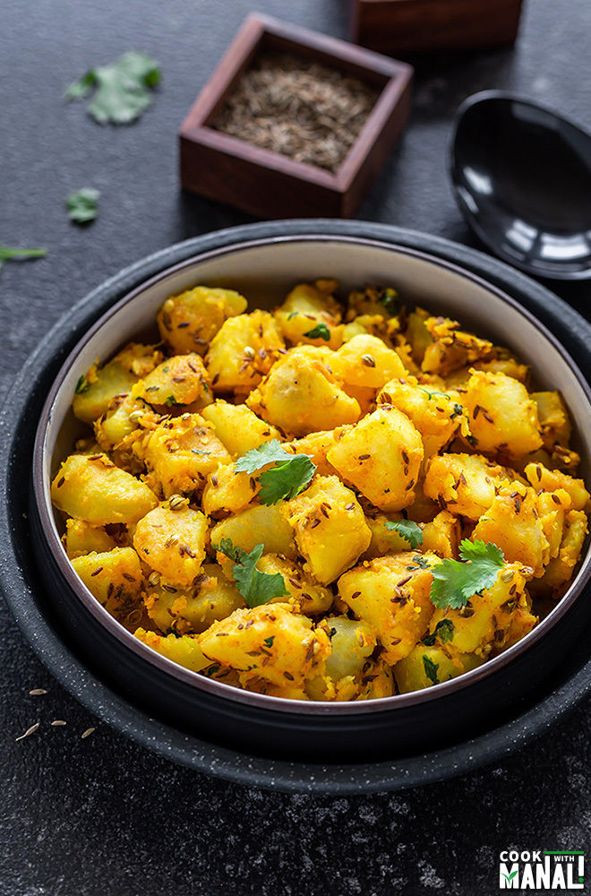 jeera aloo in a black bowl with a ladle and spice containers in the background