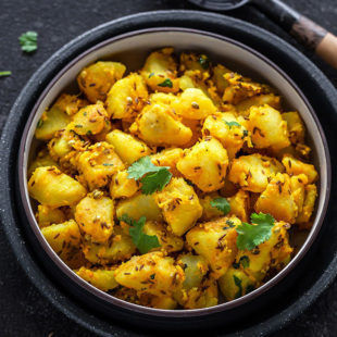 jeera aloo in a black bowl with a black wooden ladle on the side