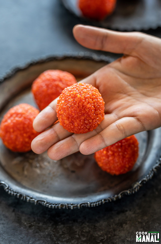 motichoor ladoo placed on an extended palm with more ladoos placed in a plate in the background
