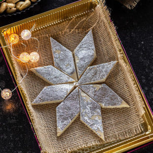 kaju katli arranged in a sweet box with small lights on the side and plate of cashews in the background