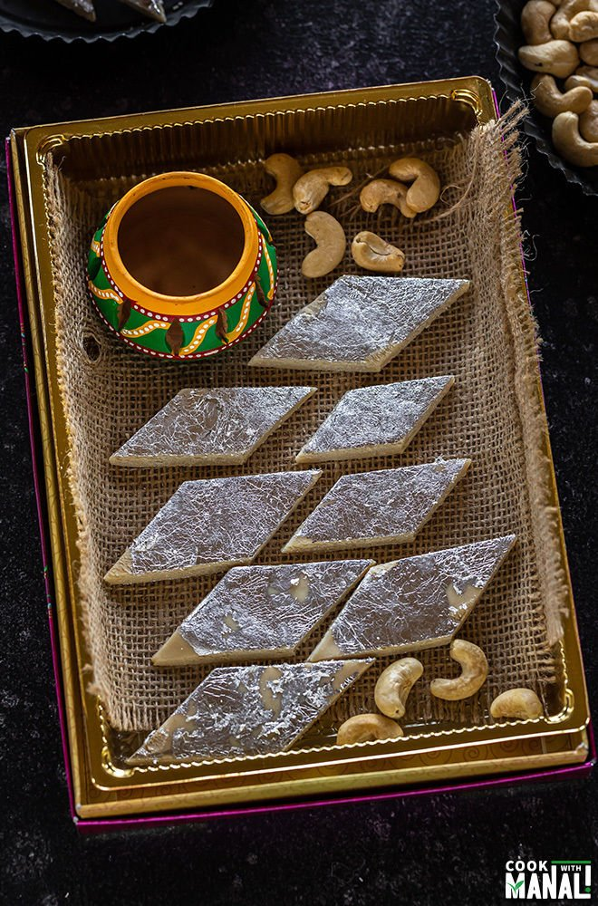 kaju katli arranged in a sweet box with some cashews on the side